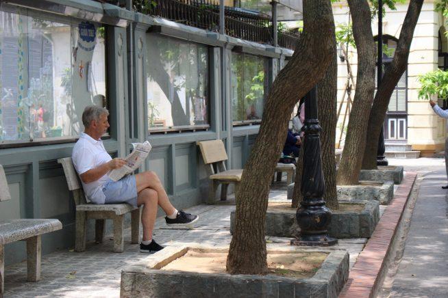ベンチで新聞を読む姿も