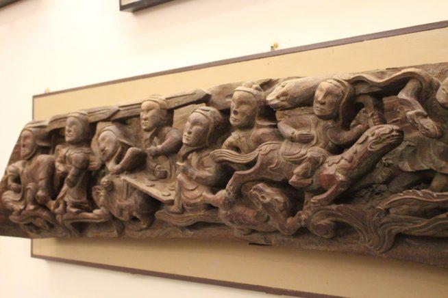 複数の人を描いた木の彫刻