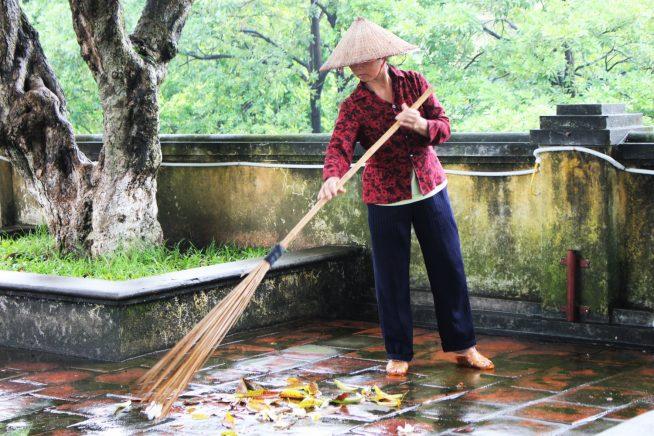 端門で落ち葉を掃くおばさん