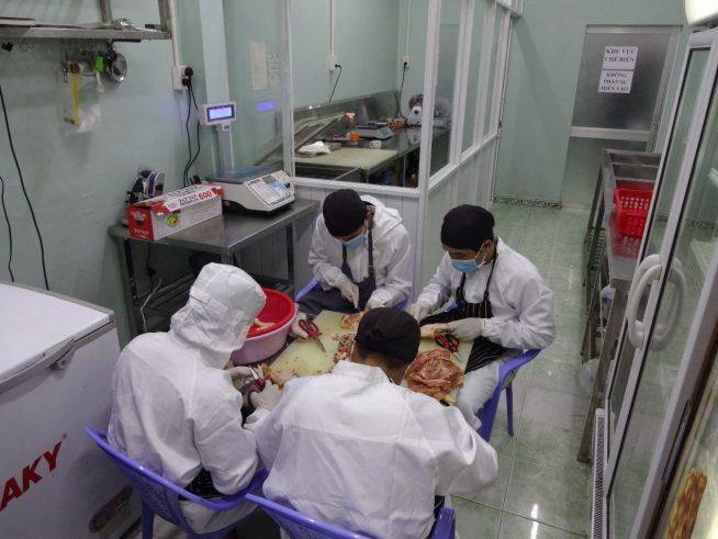 加工場で鶏肉の下処理をするベトナム人従業員
