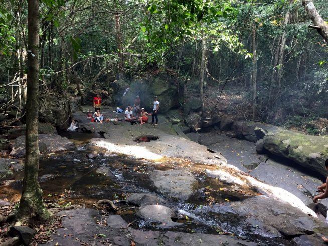 川の横でピクニックを楽しむ観光客