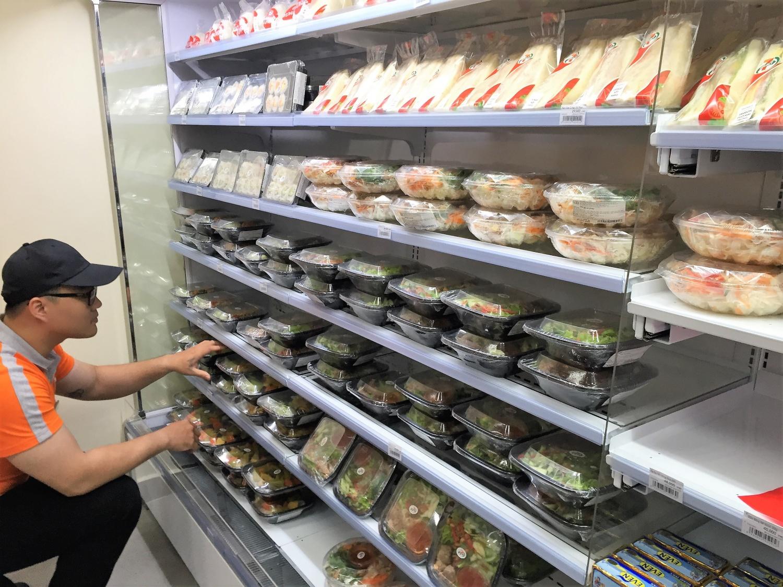 食材冷蔵コーナーは、サンドイッチやサラダ、ごはんものが売られています。店員さんが、乱れた商品を綺麗に並べています。